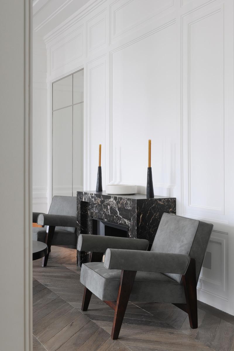 Интерьер гостиной в белом цвете. Камин из мрамора выполнен в духе ар-деко. Кресла — реплики работ Ле Корбюзье и Пьера Жаннере.