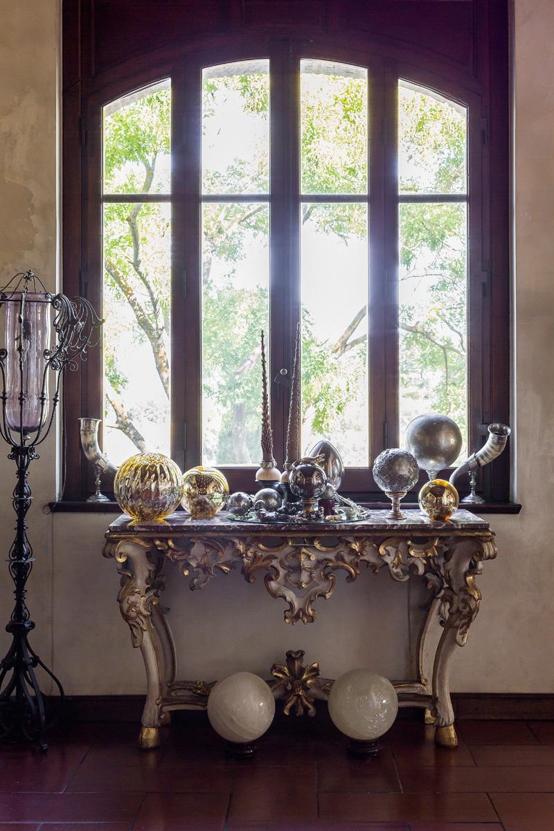На консоли выставлены украшения, статуэтки и фигурки из муранского стекла и металла из коллекции Кавалли.