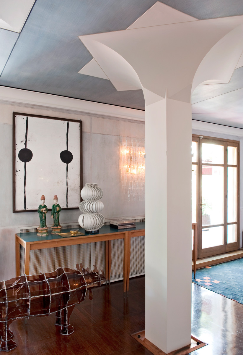Прихожая. Несущий столб архитектор Джанкарло Монтебелло превратил в колонну с необычной капителью. Консоли были разработаны Джо Понти для отеля Parco dei Principi в Сорренто. Настольный светильник, дизайн Олафа фон Бора. На стене — работа Александра Мэя.
