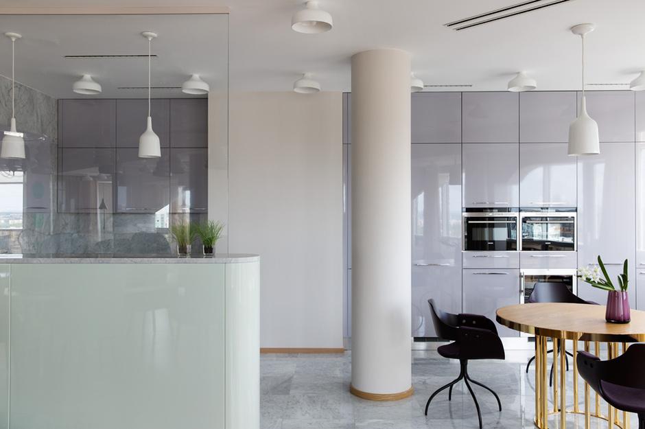 Кухню от гостиной отделяет лишь стеклянная перегородка. Кухонный гарнитур, Lube, стулья, BD Barcelona, подвесной светильник Copaсabana, Metalarte. Стол выполнен по рисунку Хайме Айона.