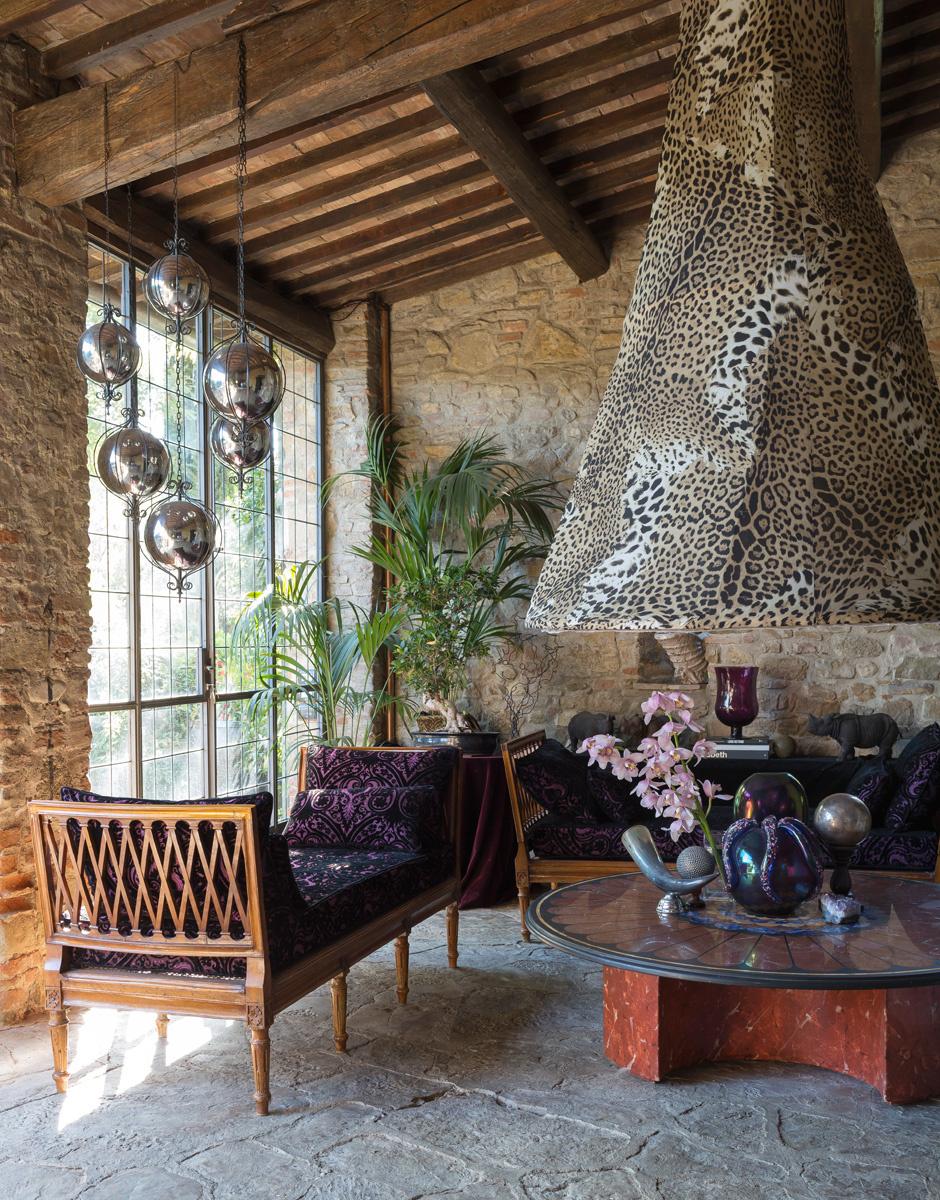 Вторая гостиная. Здесь особенно приятно находиться в жаркие дни: благодаря каменному полу и стенам в помещении царит прохлада. Идущий к потолку дымоход камина украшен фирменным леопардовым принтом Кавалли.