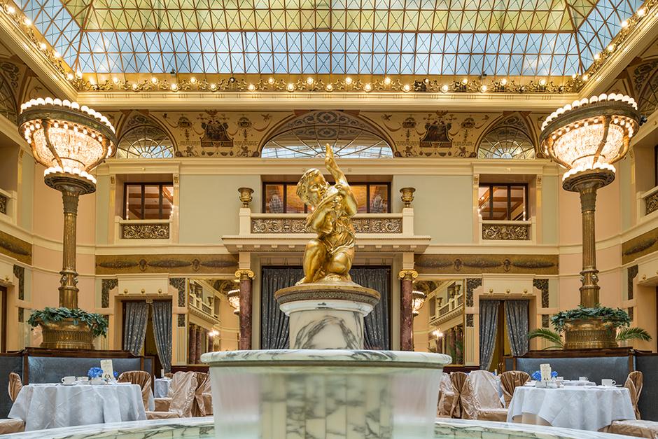 Главный зал отеля. На переднем плане — скульптура, украшающая мраморный фонтан.