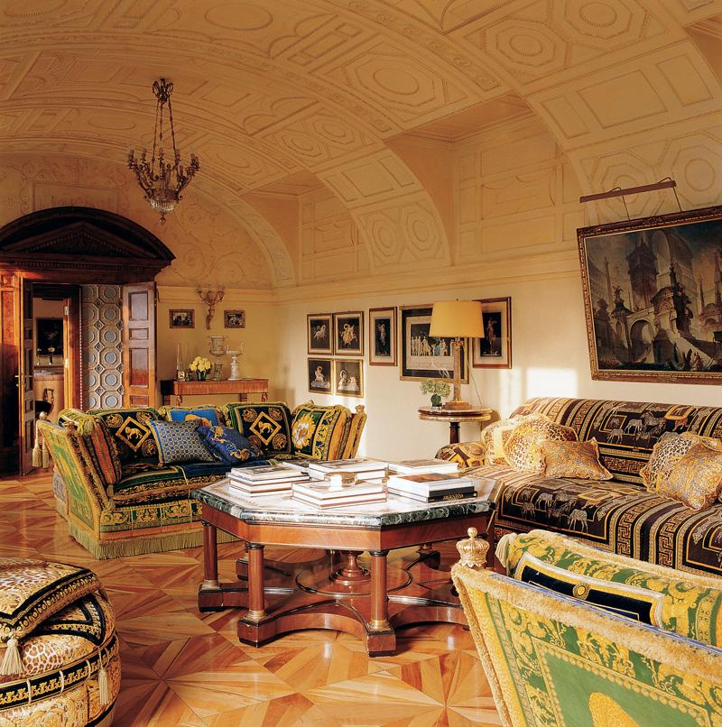 Маленькая гостиная на втором этаже квартиры. Вокруг коктейльного столика со столешницей из искусственного мрамора стоят диваны из коллекции Versace для дома. На стене — картины современного художника Миммо Паладино.
