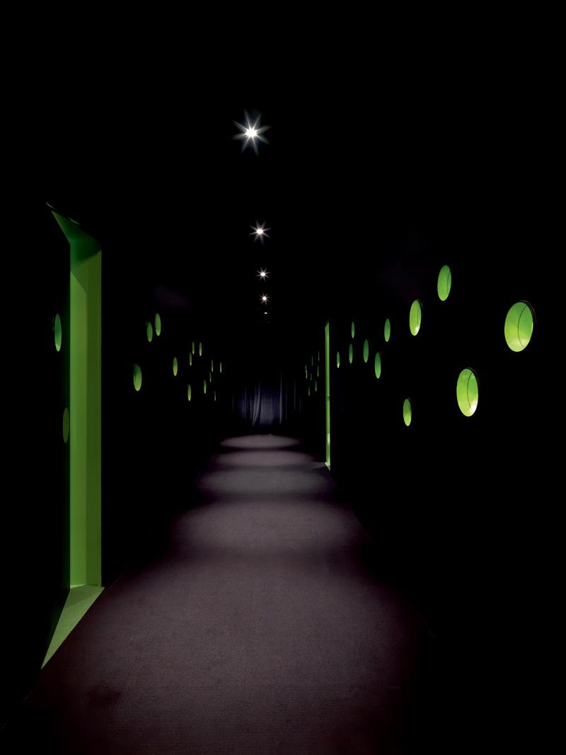 Через круглые окошки темного коридора легко заглянуть в переговорные.