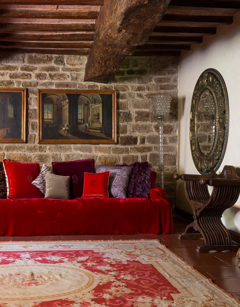 Гостиная. Хозяева оставили массивные потолочные балки открытыми, кроме того решили «обнажить» каменную кладку. Диван, подушки Venezia, Roberto Cavalli Home.
