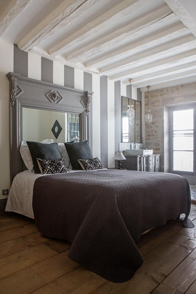 Одна из спален. Вместо изголовья кровати — старинный каминный портал, в который встроено зеркало. Стены выкрашены в серо-белую полоску — обилие вертикальных линий визуально увеличивает высоту потолка. Справа от кровати — раковина.