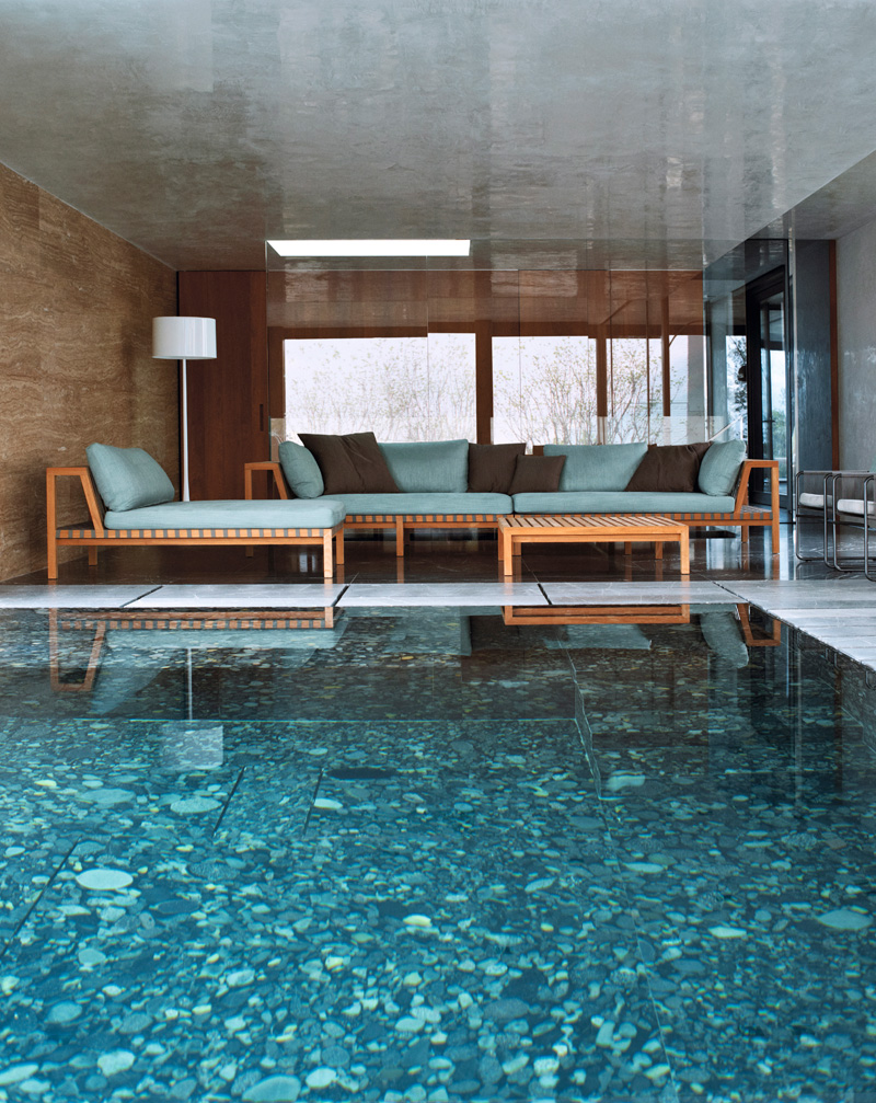 Бассейн, расположенный на террасе, продолжается внутри дома: стеклянная стена гостиной делит его на две части.