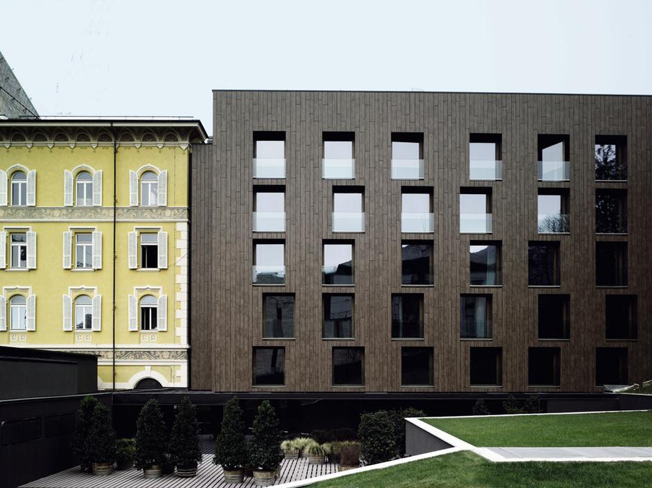Лаконичный минималистский фасад Parc Hotel Billia контрастирует с соседним зданием гранд-отеля, построенным в стиле belle époque, популярном на рубеже XIX–XX веков.
