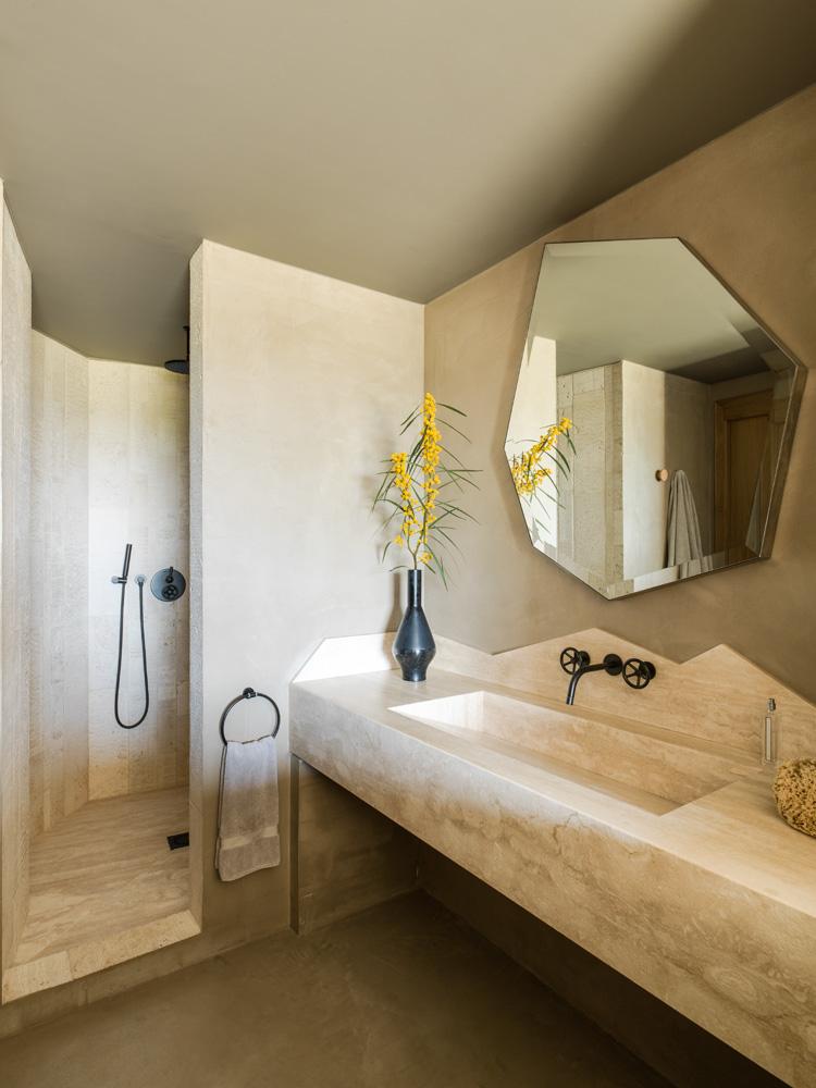 Гостевой санузел. Консоль со встроенной раковиной сделана на заказ из травертина. Этим камнем выложена и душевая. Зеркало, дизайн Жан-Луи Деньо для Pouenat.