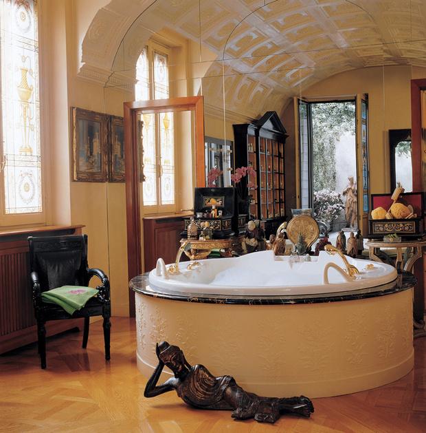 Интерьер ванной комнаты украшают обитые черной кожей кресла Vanitas из Versace Home Collection и бронзовая статуя Будды.