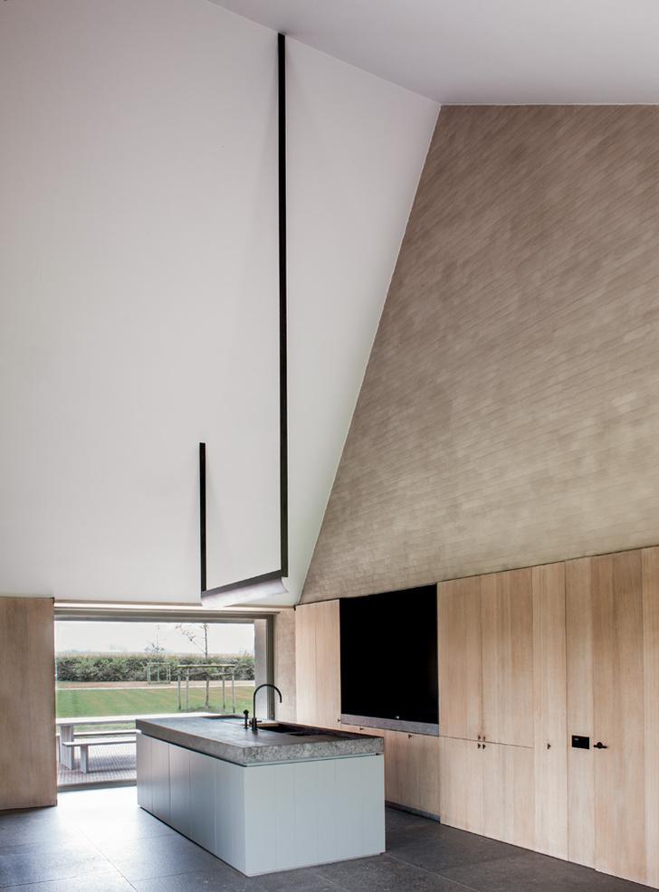 Кухня. Вертикальный объем помещения подчеркивает светильник в виде гигантской черной скобки, висящей над кухонным «островом». Мебель сделана на заказ.