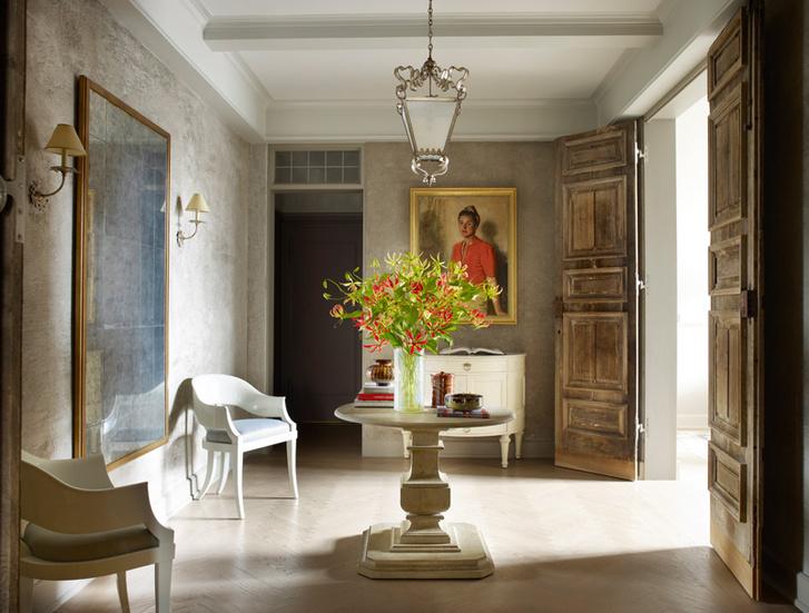 Холл в квартире Болтонов на Манхэттене. Стол с круглой столешницей— Dennis & Leen. Белые стулья, Saladino Furniture. На стенах, покрытых искусственно состаренной штукатуркой,— автопортрет художницы Эллен Эммет Ранд.