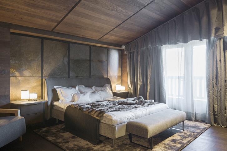 Спальня. Кровать Edel c мягким изголовьем в текстильной обивке. Прикроватные тумбочки с мраморными столешницами сделаны из дуба. Стена за изголовьем отделана панелями из камня.