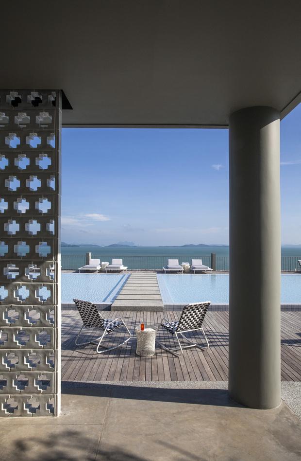 Перегородка из керамических блоков, напоминающая традиционную арабскую решетку машрабия*, отделяет террасу с бассейном от бара. Кресла-качалки, Gervasoni.