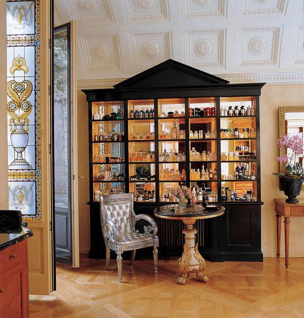 На полках шкафа с зеркальной задней стенкой расставлены флаконы духов из обширной коллекции Донателлы. На переднем плане — французский круглый стол эпохи ампир.