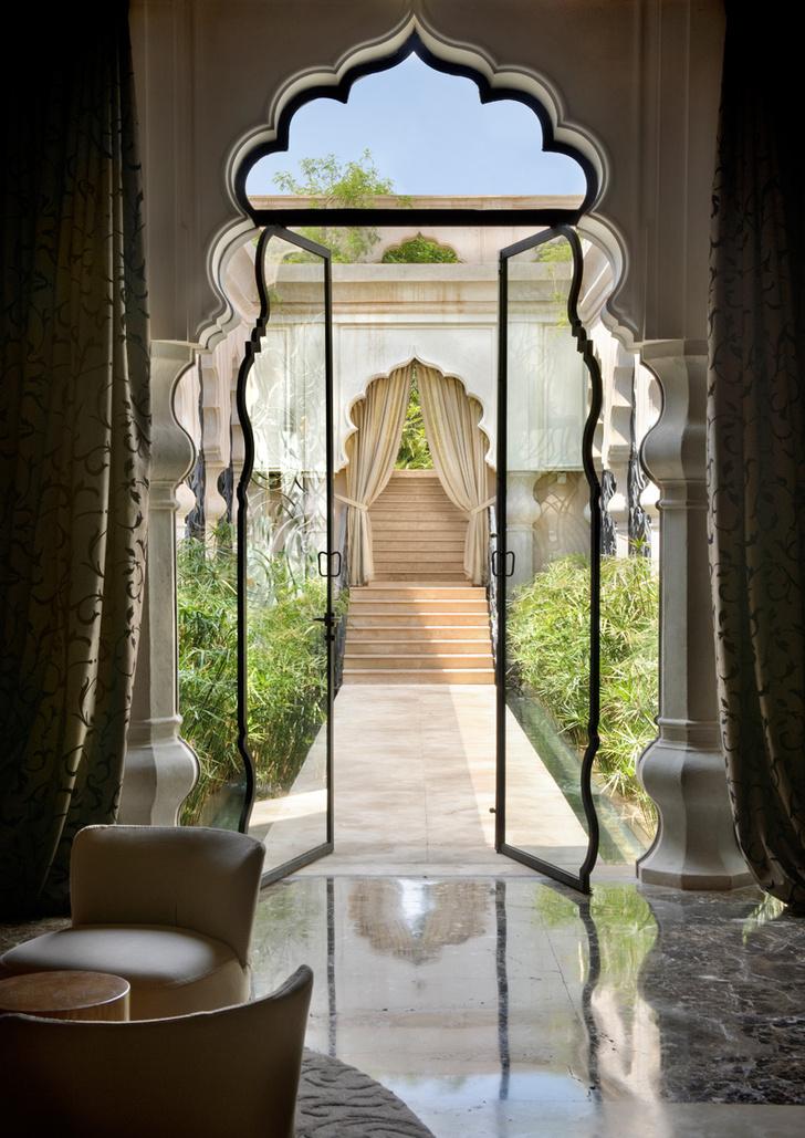 Лобби отеля. Высокие стеклянные двери помогают визуально стереть границу между интерьером и садом.