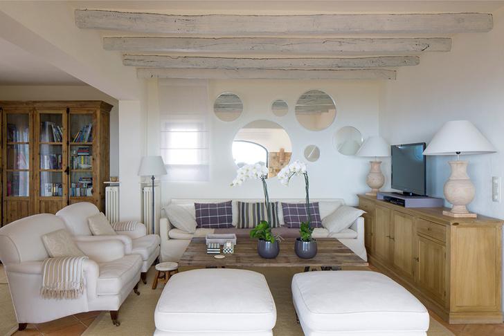 Первый этаж дома — единое пространство, состоящее из гостиной, кухни, столовой и кабинета, отделенных выступами стен. Мягкая мебель в гостиной и лампы с деревянным основанием, Becara; комод справа, Basic Line; на стене круглые зеркала разного диаметра, Branco sobre Branco.