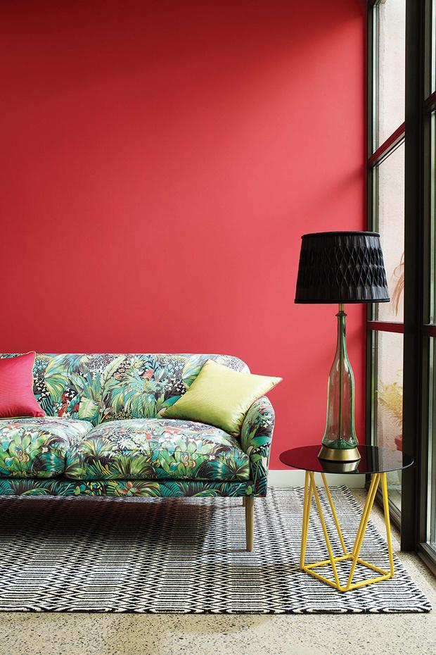 Сделать интерьер динамичным, можно выкрасив одну из стен в комнате в красный цвет. Диван в обивке тканью от Osborne & Little