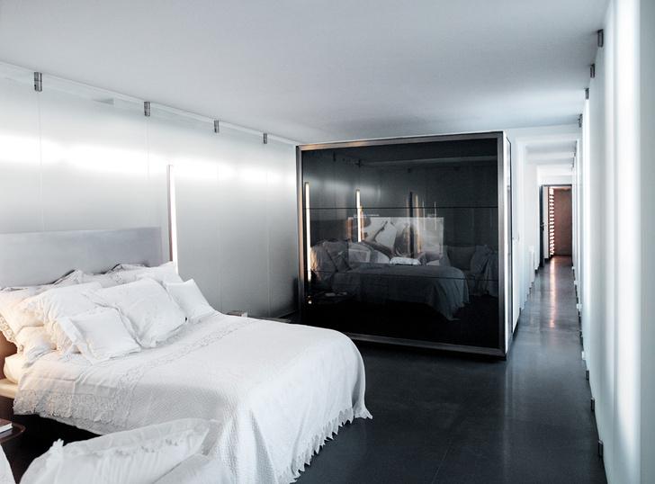 Стены спальни сделаны из матового стекла. Коридор ведет в гардеробную. Постельное белье с кружевами — ироничная уступка хозяина «мещанскому уюту».