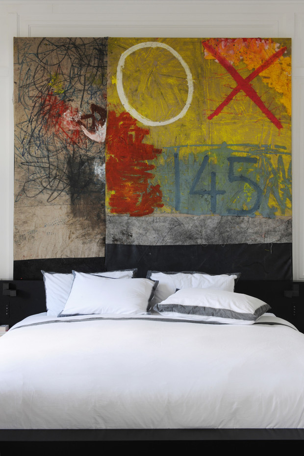 Спальня. Роль ярких акцентов в монохромном интерьере играют произведения современного искусства.