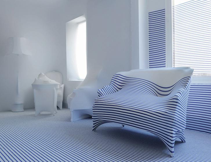 Комната апартаментов, оформленных Жан-Полем Готье по просьбе французского ELLE Decoration, выдержана в «морской» гамме. Торшеры, журнальный столик и кресла от Roche Bobois модельер обтянул эластичной тканью. Тон всему интерьеру задает ковер от Ege. Узор из синих и белых полосок переходит на кресло и стены