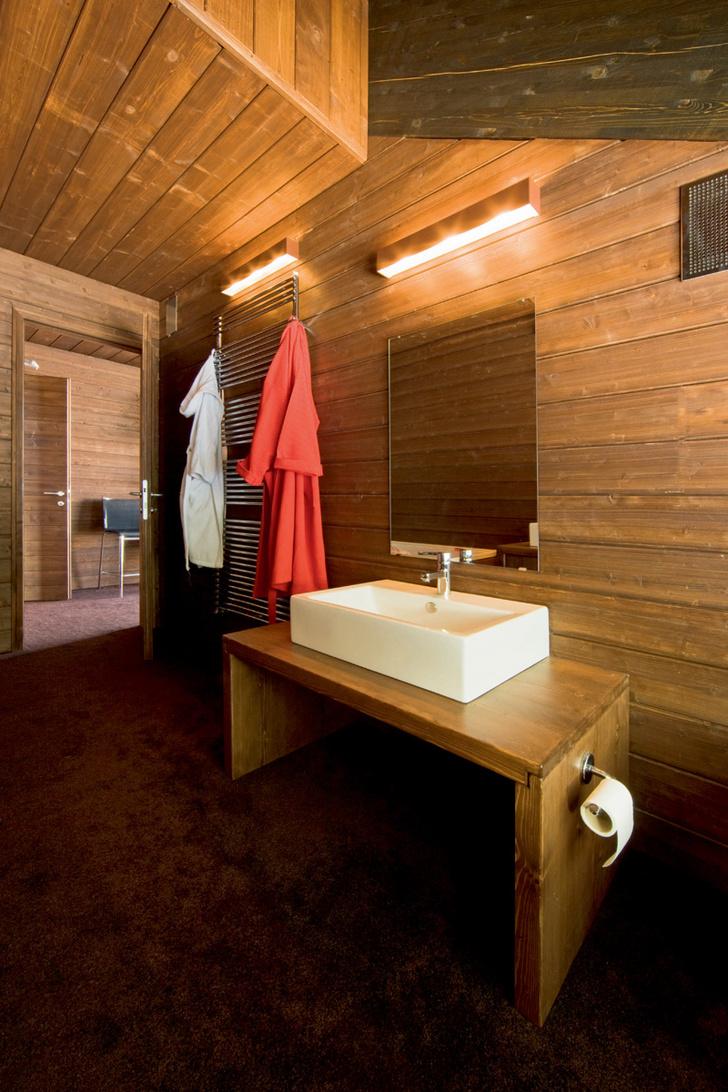 Стены ванной комнаты обшиты еловыми досками. На деревянном подстолье установлена раковина Fuori Box от Artceram со смесителем Lineare от Grohe. На стене — светильники Box от Oty Light.