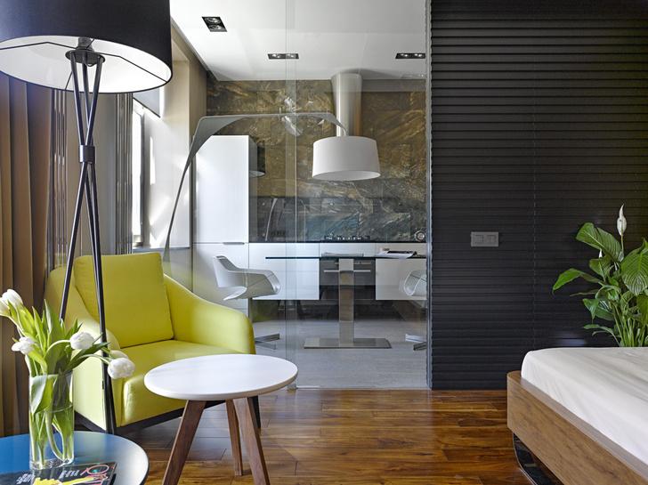 Стеклянная раздвижная дверь отделяет зону спальни от кухни и столовой. Рельефная деревянная панель изготовлена по эскизам дизайнера в его мастерской. Там же сделана корпусная мебель для кухни. Торшер с белым абажуром, южно-африканская марка OKHA Interiors. Пол — массив сукупиры*.