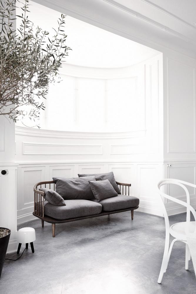 Гостиная. Диван Fly, дизайн студии Space Copenhagen для &Tradition. Cтены оштукатурены и выкрашены в белый цвет, полы — бетон. Напольный светильник на ножках Milk, похожий на крохотный табурет, спроектирован хозяином дома.