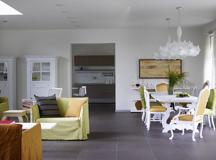 Зона столовой в гостиной. Диван, Gervasoni. Обеденный стол, стулья вокруг него, стеллаж и витрина, все — Lando. Потолочный светильник, Flos. На заднем плане — кухня, Bulthaup. Полы во всем доме выложены керамогранитом, Mosa.