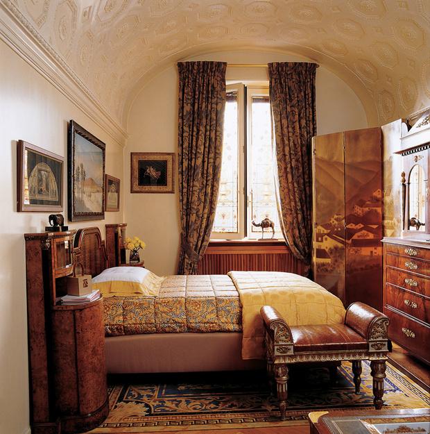 В гостевой комнате царит смешение стилей: неоклассическая ореховая кровать и прикроватный столик соседствуют с лакированной ширмой в стиле ар деко. Шторы, постельное белье, занавески, табурет и ковер — линия Versace Home Collection.