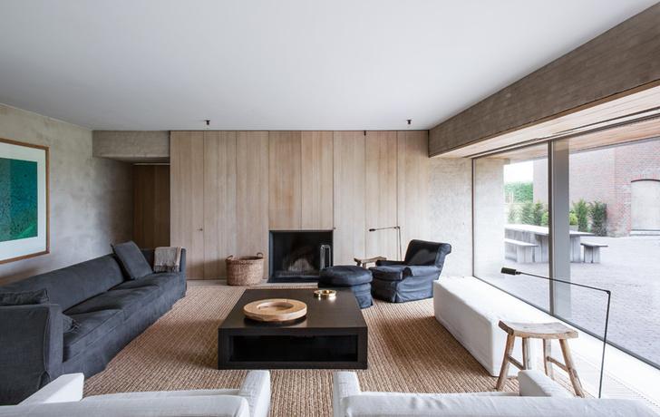 Гостиная с панорамными окнами, возникшими на месте глухой стены, выходит во двор. Стена обшита деревянными панелями с дверцами, за которыми скрываются шкафы и дымоход встроенного камина. В глубине слева — проход на кухню.