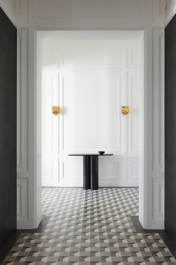 Прихожая. На полу — «ковер» из искусственного мрамора ручной работы. Консоль, дизайн Эрика Шмитта. Бра, дизайн Жюля Ваббеса.