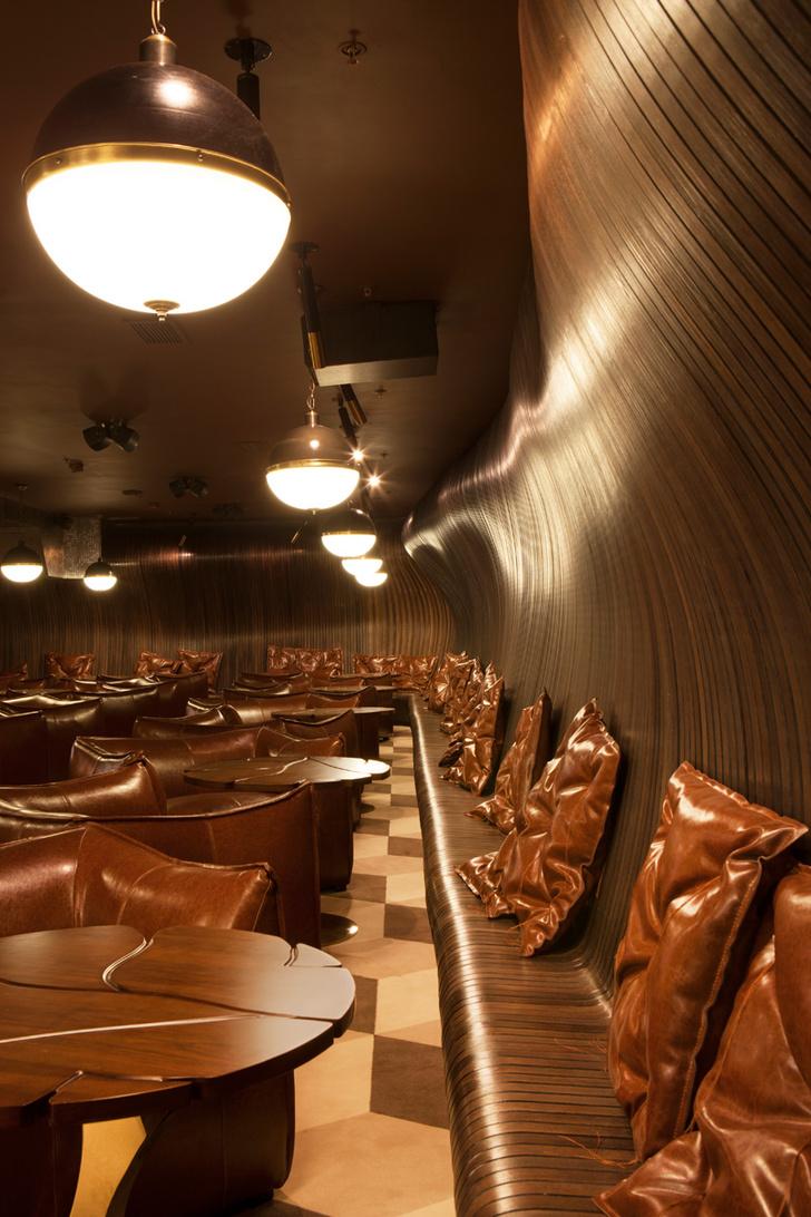 Лаунж-зона кинотеатра. Стены отделаны гнутой фанерой.