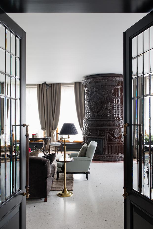 Фрагмент гостиной. Кресла, Ralph Lauren Home. Латунные ручки, шпингалеты на окнах — компания «Русский Модерн». Печь изготовлена на заказ по эскизам архитекторов. На полу — венецианская мозаика терраццо, компания «Каменный остров».