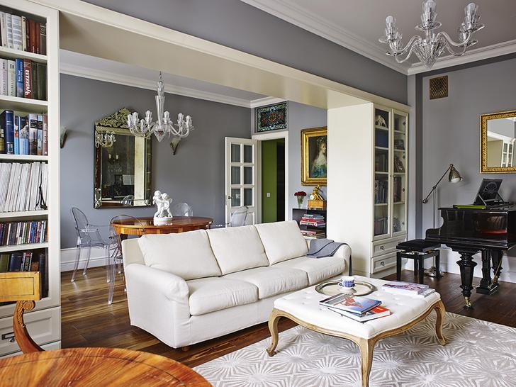 Гостиная разделена встроенными шкафами на две части – собственно гостиную с роялем и столовую. Cо стороны гостиной в шкафах хранятся книги, со стороны столовой посуда Диван, Flexform. Люстры, Humprecht, Preciosa на 6 и 12 рожков