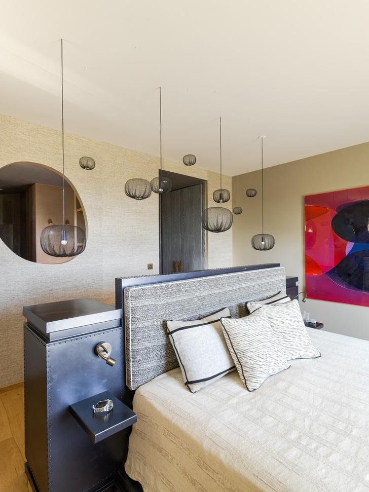 Гостевая спальня. Изголовье кровати и прикроватный столик выполнены на заказ из металла. Подушка, закрепленная на изголовье, обита тканью Obi, Romo. Лампы из полипропилена Farming-Net Lamps, Nendo. На стене — работа художника Питера Циммерманна.